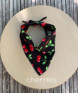 Pictured on a coardboard circle, is a small black dog bandana that features red cherries printed throughout.