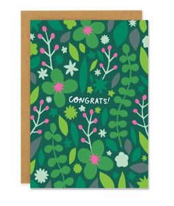 "Pictured against a white background is a brown envelope with a green card on it. The card has hand drawn illustrations of leaves, foliage, and flowers on it. THe card is mostly green, but features little pops of purple and lime green. There is text in the middle of the card that says ""congrats!"""