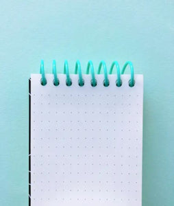 Pictured against a blue background is a notepad that features a blue coil binding at the top. The paper features a gray grid dot line format.