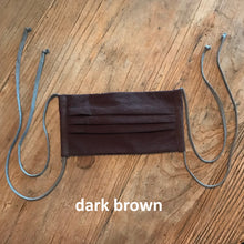 Load image into Gallery viewer, Pictured against a wooden background is a dark brown face mask that features four fabric ties.
