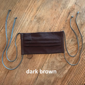 Pictured against a wooden background is a dark brown face mask that features four fabric ties.