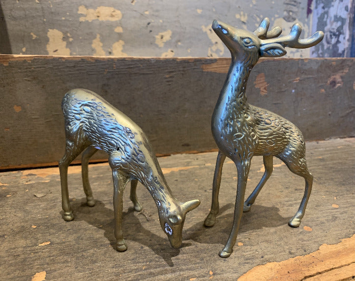 Pictured against a wooden background are two antique brass figurines of deer.