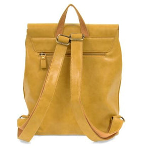 Back view of the dijon colored backpack with a small handle at the top, two adjustable straps accented with gold adjustable rings and a gold zipper for a small pocket on back. Pictured in front of a white backdrop.