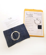 Load image into Gallery viewer, sewing pattern envelope with contents next to it, including a piece of fabric, wire and sewing instructions