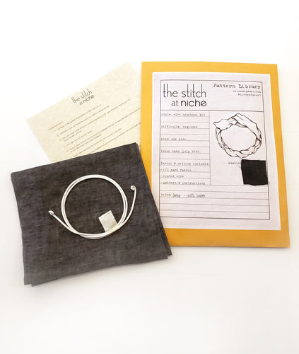 sewing pattern envelope with contents next to it, including a piece of fabric, wire and sewing instructions