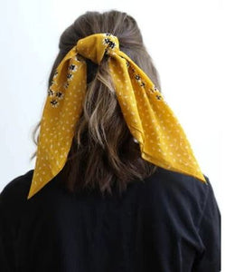 Pictured is the back of a brunette model's head. The model is wearing her hair halfway up with the yellow scarf tied around her hair.