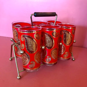 red and gold and paisley set of 6 highball glasses in a brass and wood handle carrying case against a coral background