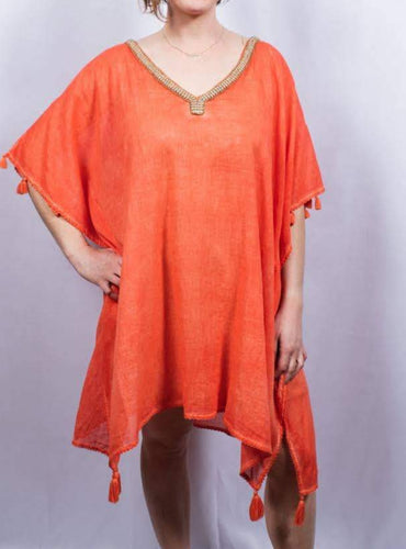 close-up of model wearing a coral poncho with gold trim on the v-neck neckline and small tassels on sleeves and hem. Against a light grey background.