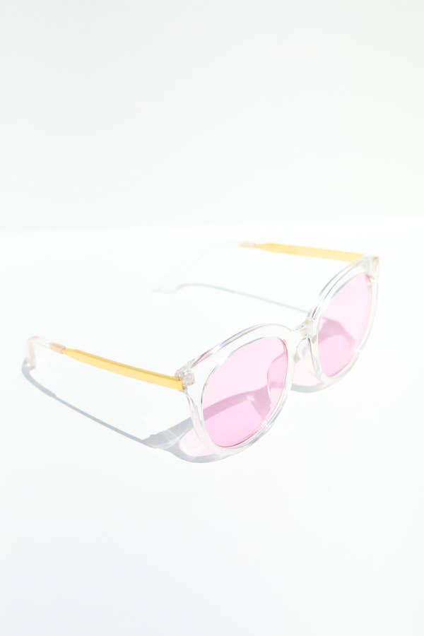 clear framed sunglasses with a gold tinted arm and pink tinted frames