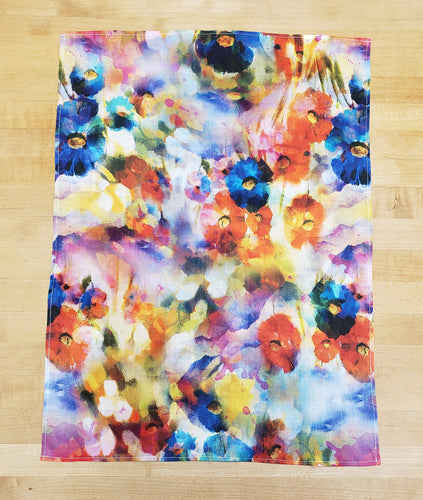 multicolor floral print dish towel on a wood background