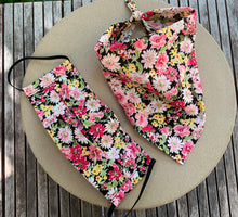 Load image into Gallery viewer, Pictured against a cardboard circle, is a small dog bandana with floral print featuring mostly pink, dark pink, and yellow floral print. There is a matching face mask to the left of it.