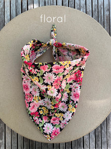 Pictured against a cardboard circle, is a small dog bandana with floral print featuring mostly pink, dark pink, and yellow floral print.