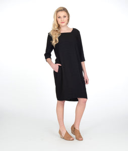model in a black shift dress with 3/4 sleeves and a squared neckline