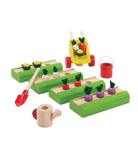 Wooden set including four green raised beds, a wooden shovel, wooden watering can, wooden wheelbarrow, and wooden watering can. Also pictured are assorted wooden vegetables. Pictured against a white backdrop.