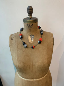 Pictured is a brown body form wearing an adjustable necklace that is fully tightened to feature how short it can be worn. The necklace features a black cord and cube and sphere shaped resin beads that are spaced out on the cord and multicolored in black, white, and red, patterns. The body form is pictured in front of a white wall.