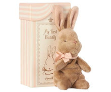 Load image into Gallery viewer, sweet brown bunny plush with a pink bow on it's neck, in front of an ivory and pink striped box