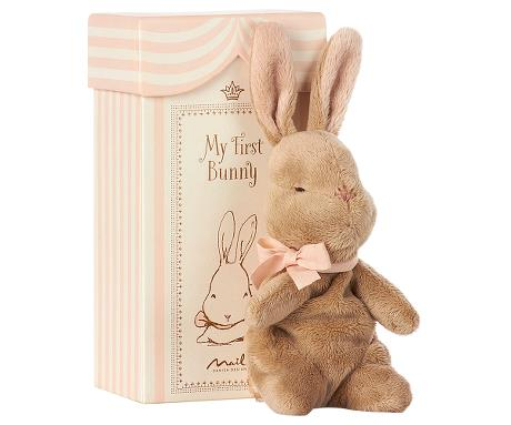 sweet brown bunny plush with a pink bow on it's neck, in front of an ivory and pink striped box