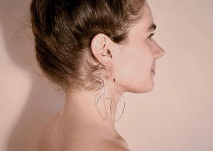 Silver wired earrings in the form a woman's body on the ears of a caucasian model.