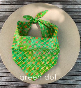 Pictured on a coardboard circle, is a small green dog bandana that has various sized orange colored dots on it.