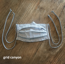 Load image into Gallery viewer, Pictured against a wooden background is a black and white grid patterned mask with four fabric ties on it.