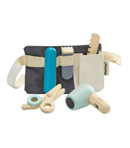 Play hairdresser set that includes a navy blue utility belt. On the belt, there is are several wooden toys: a blue hair straightener, clippers, wooden comb, wooden scissors, and a baby blue blow dryer. Pictured against a white background.