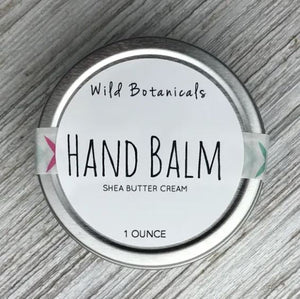 "Pictured against a grey wooden background is a round silver tin with a label that says, ""Wild botanicals hand balm shea butter cream 1 ounce"""