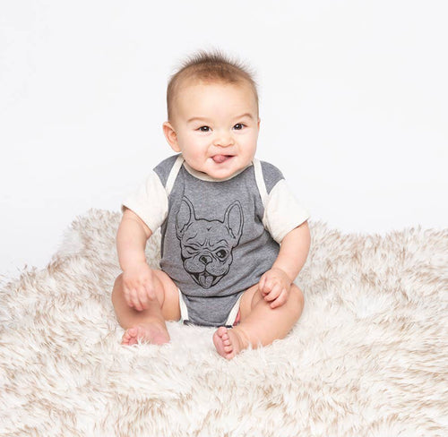 baby sitting on cream fur rug against a white background wearing grey onesie with cream sleeves and trim. onesie has black drawing print of french bulldog winking