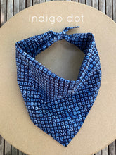 Load image into Gallery viewer, Pictured on a coardboard circle, is a small blue dog bandana that has white printed pattern on it.