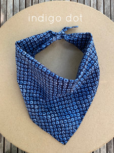Pictured on a coardboard circle, is a small blue dog bandana that has white printed pattern on it.