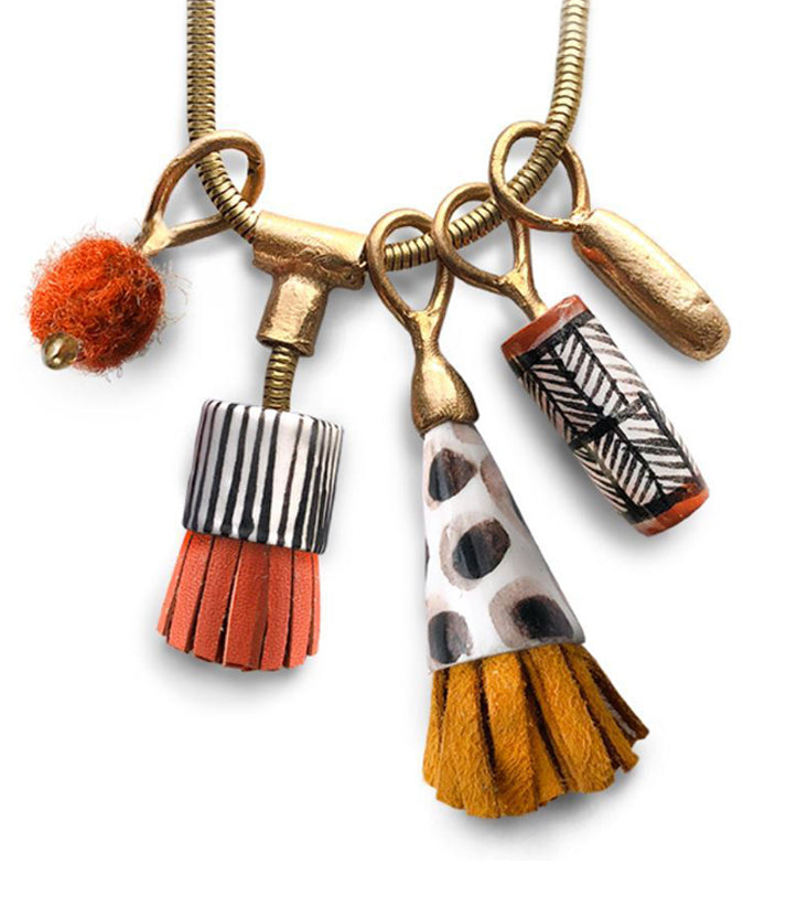 Pictured against a white background is the close up detail of the necklace charms. There is a gold chain with five charms attached. The charms include a fuzzy orange pom, a handcut orange tassel with white ceramic base, a handcut yellow tassel with cone shaped ceramic cone, a ceramic rectangle handpainted in black and white stripes, and a golden nugget.