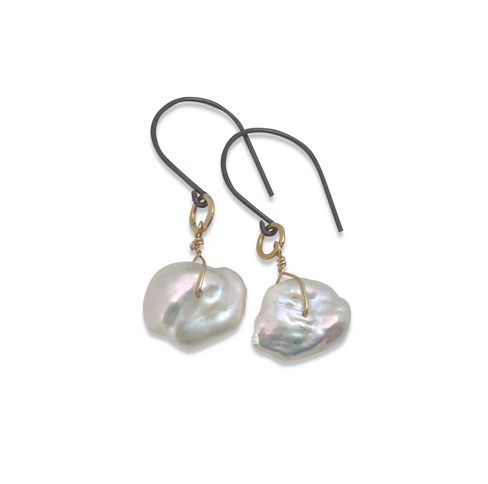 close up of keshi pearl earring with gold wire and gunmetal ear hook against a white background
