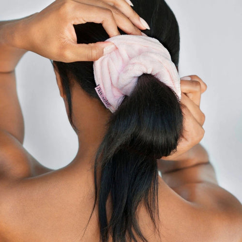 model with a pink towel scrunchie around her ponytail