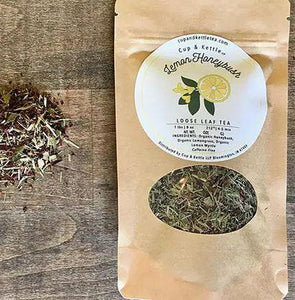 "There is a small circular mound of loose leaf tea on the left side of the photo and a brown bag labeled ""lemon honeybush loose leaf tea"" to the right. Pictured against a wooden backdrop."