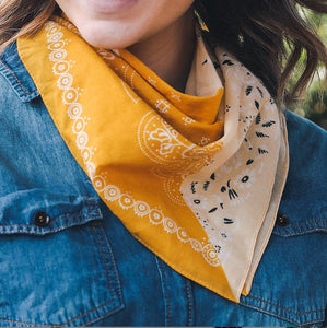 close up of model wearing a yellow and mustard bandana with black floral print tied around her neck. Against a drak denim jacket. Only her chin and ends of her brown hair are visibible in the photo.