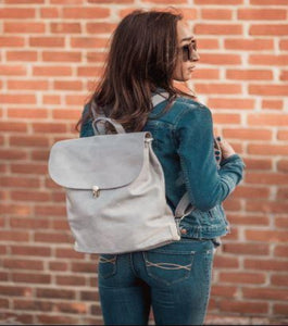 Pictured against a brick background is the back of a model with long brown hair wearing a denim jacket and blue jeans. Featured is a light denim colored, pleather backpack that the model is wearing over her shoulders.