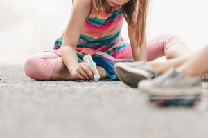 Close-up of child sitting on asphalt drawing with large piece of chalk. Child is wearing stripe sleeveless top and pink leggings. Out of focus shows from another child are in the foreground.