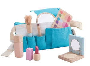 Pictured is a wooden makeup set that features a blue utility belt, pretend makeup palette, mirror, compact, perfume bottle, lipstick, eyeliner, and makeup brush. Pictured against a white background.