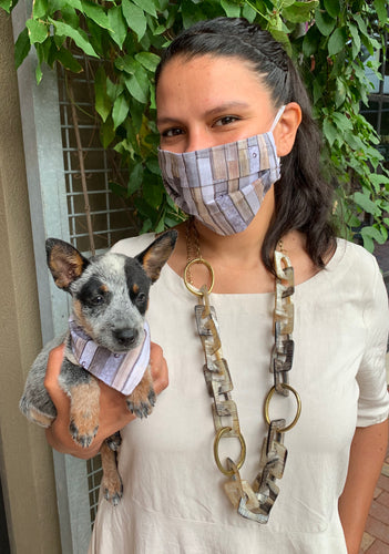 Pictured in an outdoor setting is a female model with long brown hair wearing a beige dress and a face mask with a print that resembles wood grain on it. She is holding a small blue heeler puppy that is wearing a bandana matching her mask that is printed to look like wood grain material.