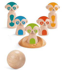 A set of five bowling pins made out of wood, that look like meerkats. Each meerkat is painted a different color and there is a solid wooden ball. Pictured against a white background.