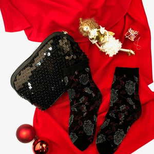model in a black sheer sock with a red and silver metallic pattern, on a decorative holiday themed setting