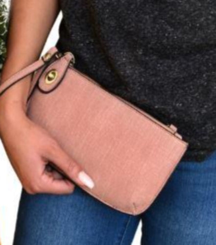 Pictured is the torso of a model holding the pink faux linen clutch in her hand with the wristlet attachment worn around her wrist.