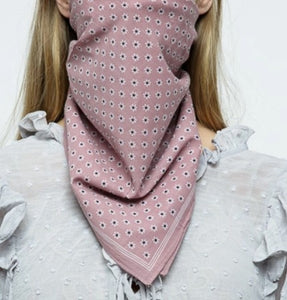 close up of light pink scarf with tiny white daisies with black center and a small stripe border. Tied on model as a mask. Model wearing a light blue polka dot ruffle shoulder top and has blond hair. White background.