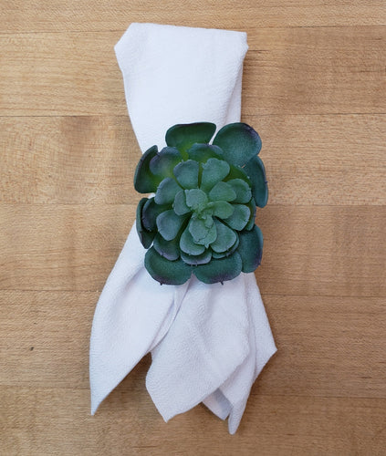 a white napkin with a fake succulent napkin ring