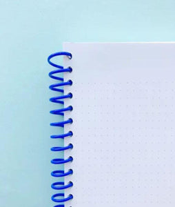 Pictured against a light blue background is a notebook that features a blue coil binding. The paper features a grid dot line format.