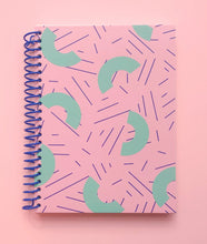 "Load image into Gallery viewer, Pictured against a light pink background is a pink notebook. The notebook features a blue coil binding and light pink half moon shaped ""noodles"" on the cover."