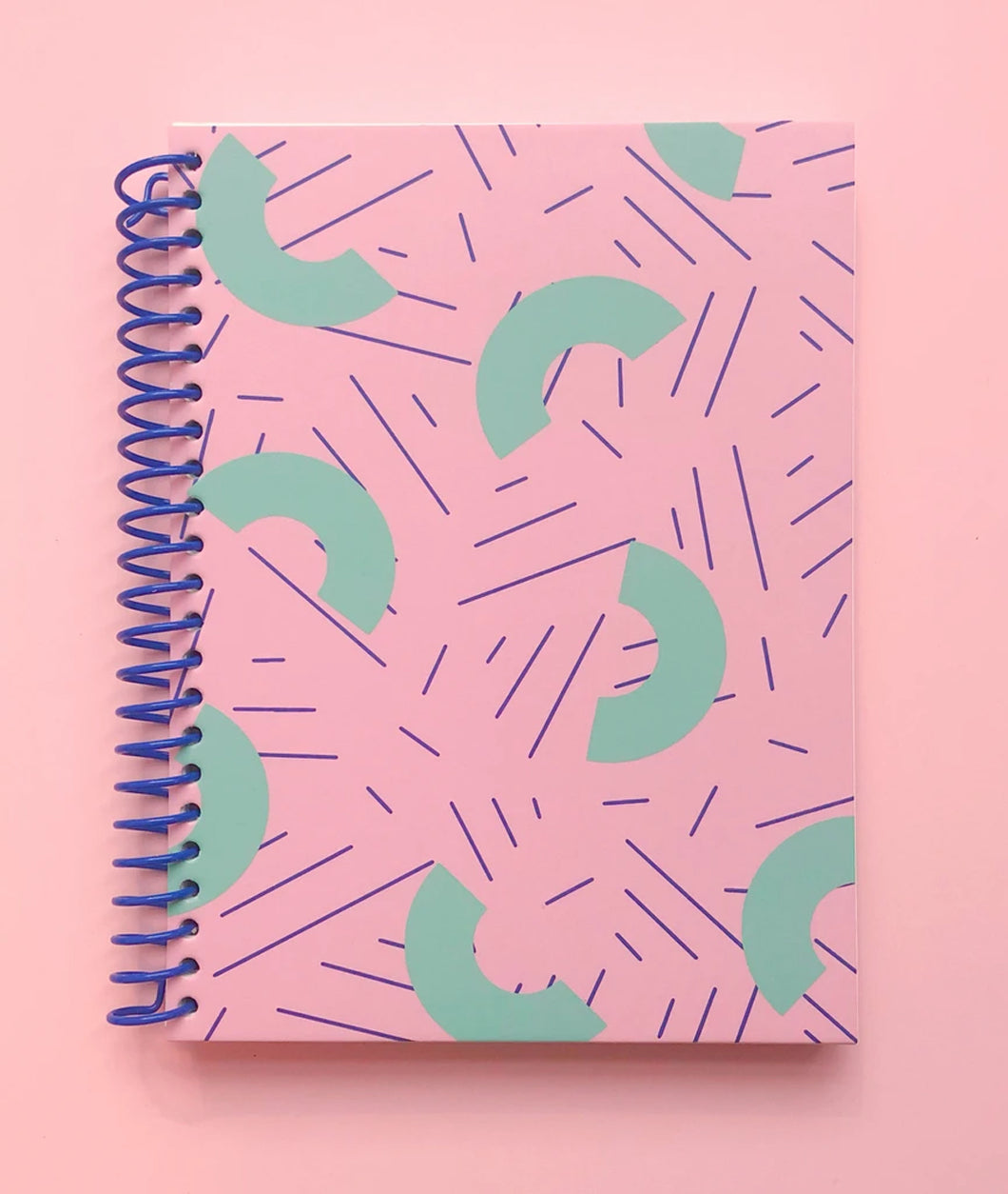 Pictured against a light pink background is a pink notebook. The notebook features a blue coil binding and light pink half moon shaped