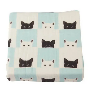 blanket with print of black and white cats and white and aqua squares