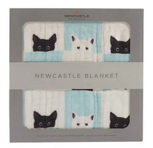 grey box containing blanket with print of black and white cats and white and aqua squares
