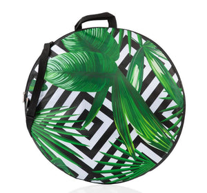 Round water resistant blanket featuring geometric black and white print and tropical leaves against a white backdrop. This photo features the blanket in it's zip up case with handles.