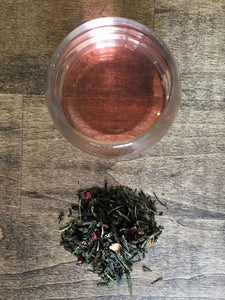 At the top of the photo, there is a clear glass of rose colored tea. Below the glass of tea is a small mound of loose leaf tea. They are pictured against a wooden backdrop.